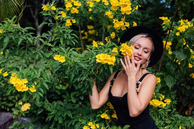 Mulher bonita e elegante caucasiana feliz em um vestido preto e chapéu clássico no parque cercado por flores amarelas tailandesas