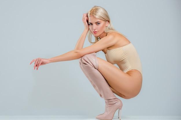 Mulher bonita e elegante com botas de salto alto, posando no estúdio. detalhe de roupa de botas de mulher elegante da moda. mulher sexy com botas de cano longo.