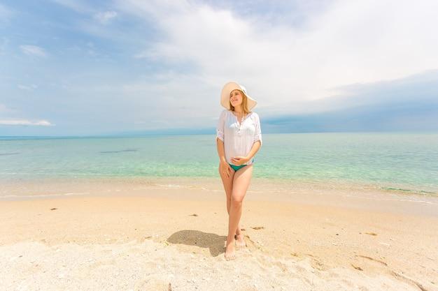 Mulher bonita e elegante com camisa branca e chapéu posando na praia em dia de sol