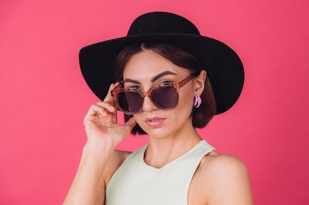 Mulher bonita e elegante com chapéu e óculos escuros posando sobre uma parede rosa vermelha
