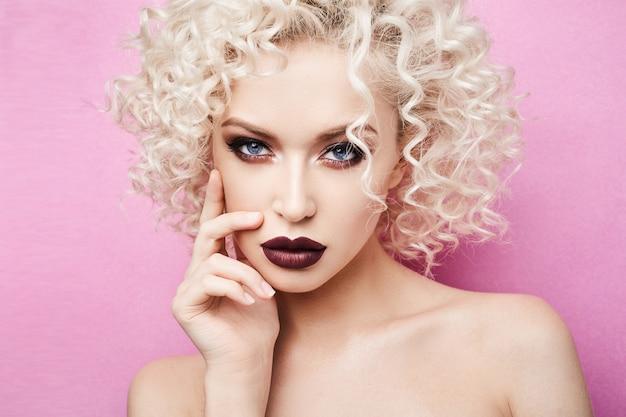 Mulher bonita e elegante, com incríveis olhos azuis, cabelo loiro encaracolado e maquiagem profissional brilhante