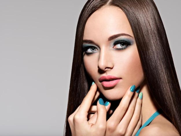 Mulher bonita e elegante com maquiagem e unhas turquesa - pose