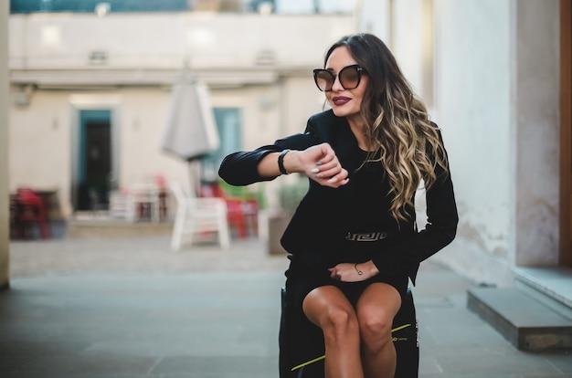 Mulher bonita e elegante com óculos escuros, sentado na mala na cidade.