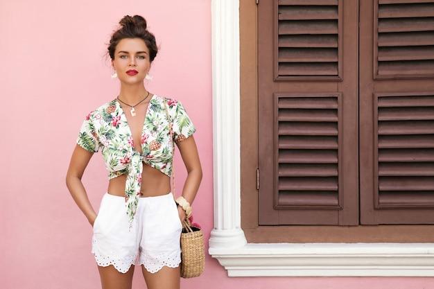 Mulher bonita e elegante com roupas de verão posando ao lado da casa com uma parede rosa