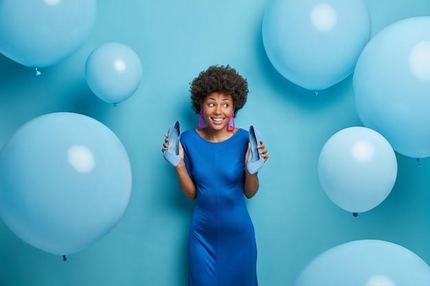 Mulher bonita e elegante de vestido azul, segura sapatos de salto alto, gosta de comemorar, se diverte na festa, parece com sorriso de lado, posa em torno de balões. senhora afro-americana usando roupas da moda