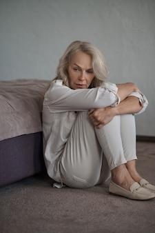 Mulher bonita e elegante, deprimida e assustada, sentada no chão acarpetado ao lado da cama e abraçando os joelhos