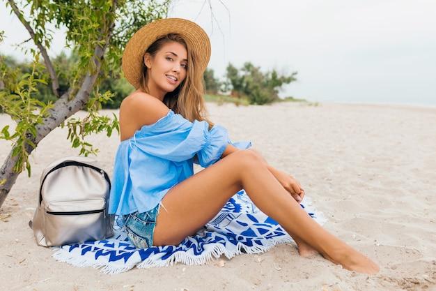Mulher bonita e elegante e sorridente sentada na areia com pernas magras nas férias de verão na praia tropical usando chapéu de palha, mochila prata