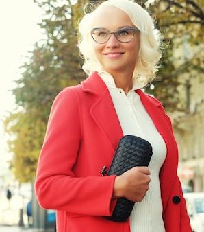 Mulher bonita e elegante em pé na rua da cidade. dia de outono.