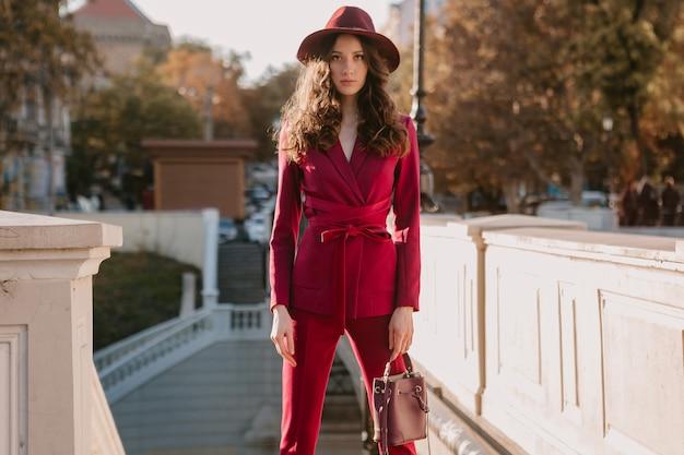 Mulher bonita e elegante em um terno roxo andando na rua da cidade, primavera verão outono temporada tendência da moda usando chapéu, segurando bolsa