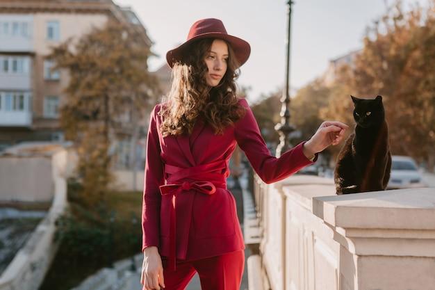 Mulher bonita e elegante em um terno roxo na rua da cidade, primavera verão outono temporada tendência da moda usando chapéu, olhando para um gato