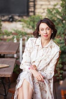 Mulher bonita e elegante em um vestido bege, bebendo café ao ar livre no café. retrato de mulher feliz em um café ao ar livre