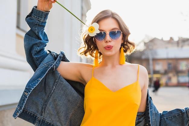Mulher bonita e elegante hippie se divertindo, moda de rua, segurando uma flor, vestido amarelo, jaqueta jeans, estilo boho, tendência da moda primavera-verão, óculos de sol, sorrindo, ensolarado, glamour