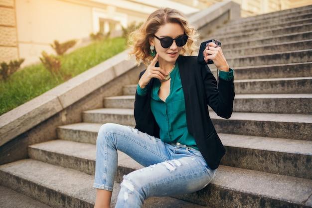 Mulher bonita e elegante jovem sentada na escada em uma rua da cidade, vestindo jeans, jaqueta preta, blusa verde, óculos escuros, segurando a bolsa, estilo elegante, tendência da moda de verão, sorrindo
