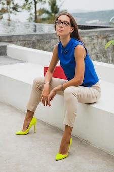 Mulher bonita e elegante jovem, tendência da moda de verão, blusa azul, bolsa vermelha, óculos, resort em uma vila tropical, férias, glamour, pernas longas e finas, calças, sapatos amarelos, salto alto