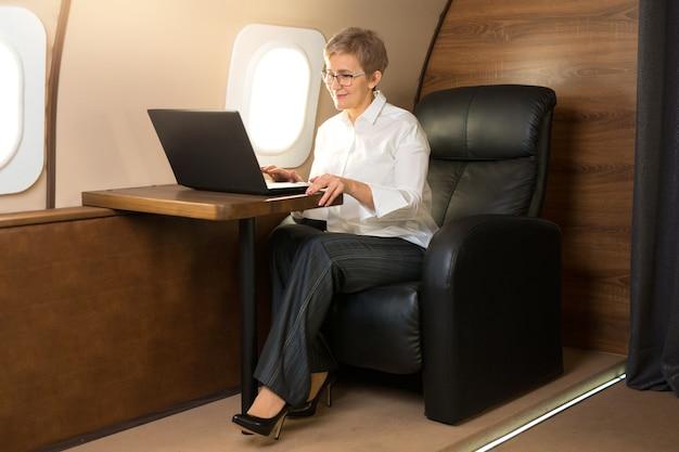 Mulher bonita e elegante na cabine de um avião particular