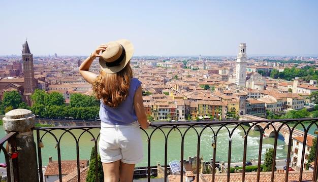 Mulher bonita e elegante na varanda, apreciando a paisagem urbana de verona. banner panorâmico com garota feliz no terraço em verona, itália.