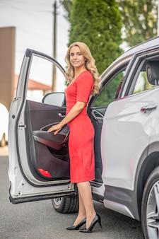 Mulher bonita e elegante perto da porta do carro aberta