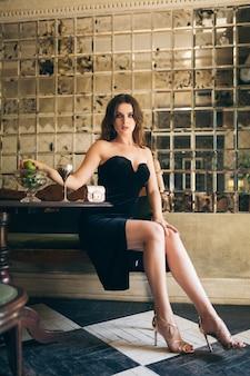 Mulher bonita e elegante sentada em um café vintage com vestido de veludo preto, vestido de noite, senhora rica e elegante, tendência da moda elegante, aparência sexy e sedutora, figura magra atraente com pernas longas em saltos altos