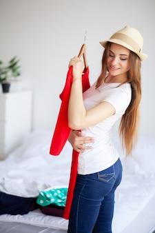 Mulher bonita é embalagem de roupas na mala em casa.