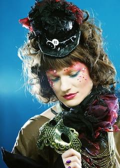 Mulher bonita e encaracolada com máscara. semblante de carnaval. foto de férias.