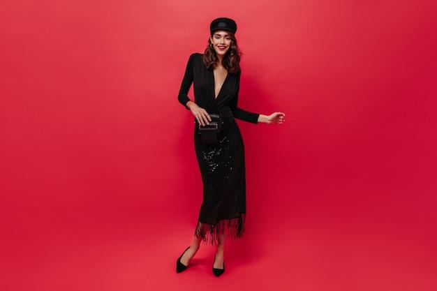 Mulher bonita e encaracolada com saia brilhante, blusa preta e boné segurando a bolsa de mão, sorrisos e poses na parede vermelha