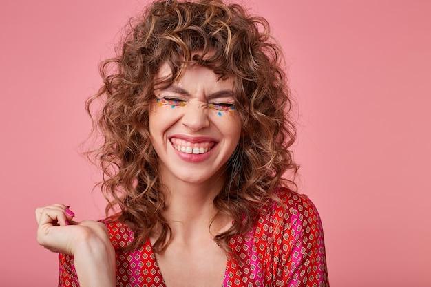Mulher bonita e encaracolada com um sorriso largo, rindo de algo com os olhos fechados, vestindo roupas listradas, em pé