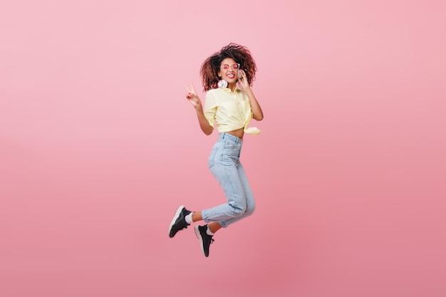 Mulher bonita e encaracolada na camisa amarela, expressando emoções felizes com um sorriso. garota magnífica hipster africana pulando.
