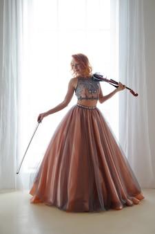 Mulher bonita e esguia com violino