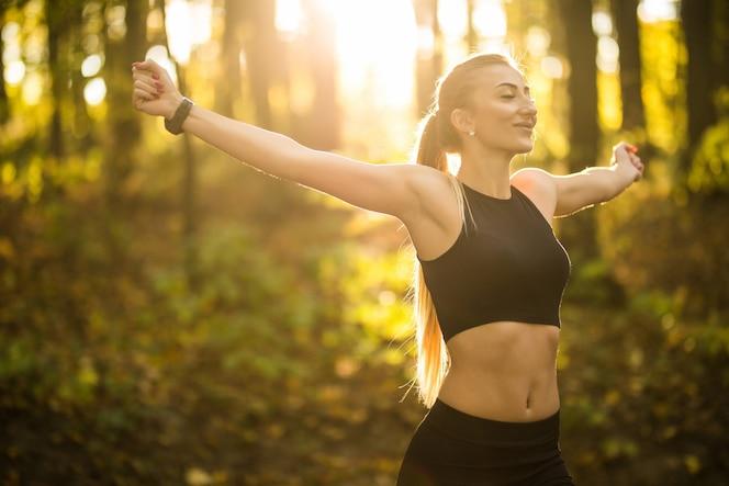 Mulher bonita e esportista fazendo exercícios de ioga no parque