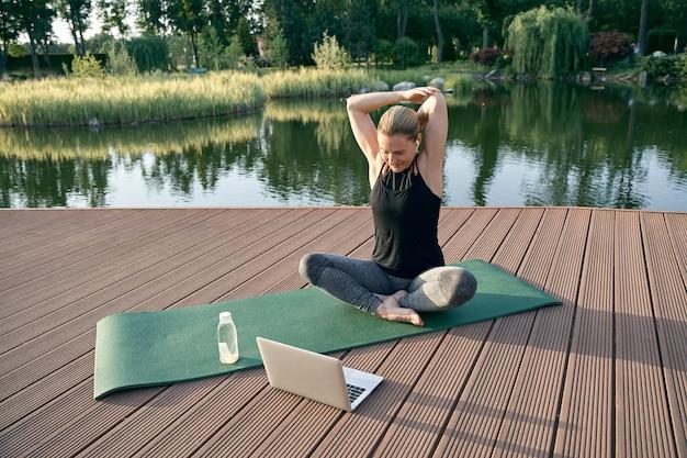 Mulher bonita e esportiva iniciante se exercitando assistindo a vídeos instrutivos em um laptop enquanto faz