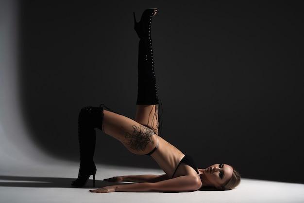Mulher bonita e esportiva posando no estúdio em um fundo preto e branco.