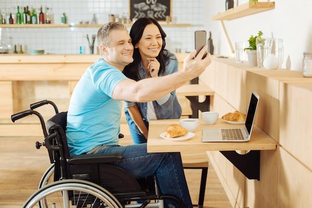 Mulher bonita e exuberante de cabelos escuros e um homem bonito e alegre, com deficiência, sentado à mesa em um café, tirando selfies e tomando café