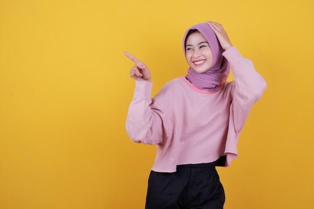 Mulher bonita e feliz apontando algo vestindo uma camiseta rosa suave