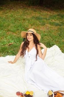 Mulher bonita e feliz com chapéu de aba e vestido branco, de pé e segurando uma cesta de pão no parque de verão