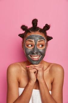 Mulher bonita e feliz cuida bem da pele, aplica máscara facial para rejuvenescimento, mantém as mãos pressionadas contra o queixo, usa toalha, penteava coques no cabelo, olha de lado. mimos, bem-estar