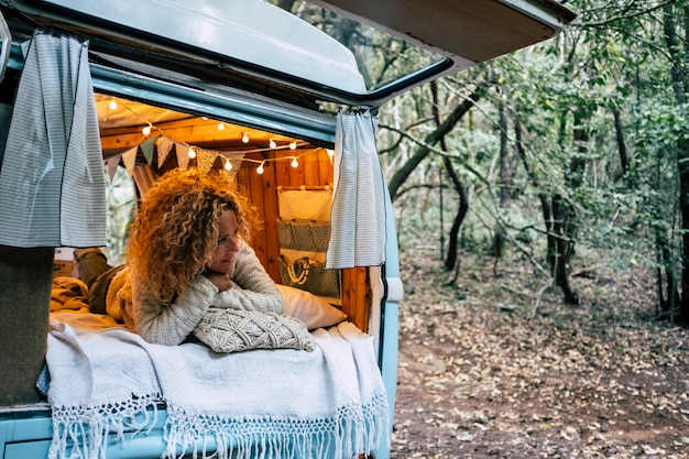 Mulher bonita e feliz e livre deite-se e relaxe dentro de seu veículo furgão azul estacionado na floresta