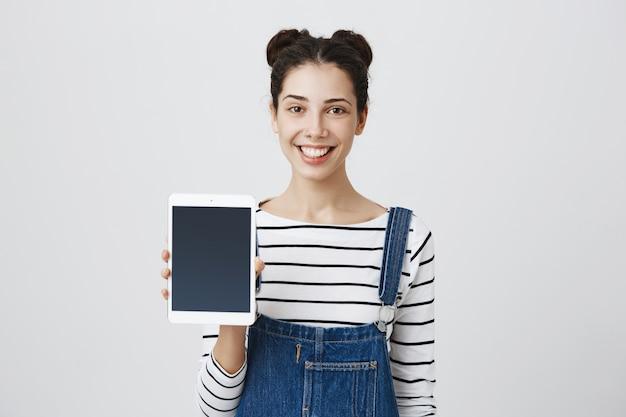 Mulher bonita e feliz mostrando a tela do tablet digital