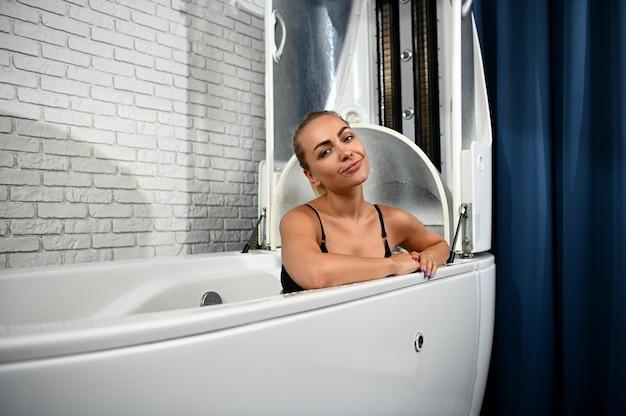 Mulher bonita e feliz sorrindo para a câmera enquanto desfruta de hidromassagem e tratamentos de beleza em uma cápsula de spa moderno no centro de spa