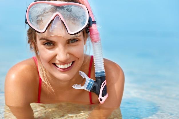 Mulher bonita e feliz usa máscara de mergulho, nada na piscina, posa em água azul pura, tem um sorriso positivo, envolvido no estilo de vida ativo. mulher desportiva snorkels debaixo de água. atividades aquáticas