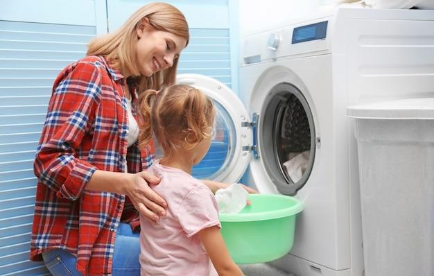 Mulher bonita e filha lavando roupa em casa
