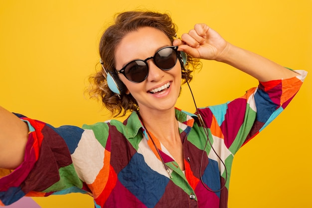 Mulher bonita e fofa com fones de ouvido mandando beijo para a câmera e fazendo autorretrato sobre parede amarela