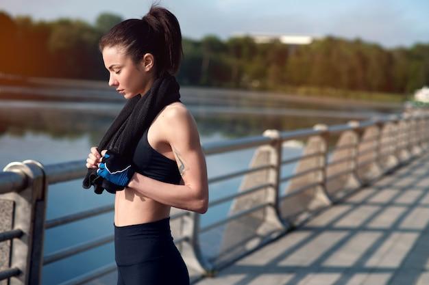 Mulher bonita e forte jovem descansando depois de um treino ativo no parque de verão. conceito de esportes. estilo de vida saudável