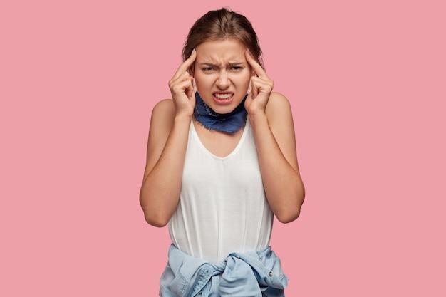 Mulher bonita e frustrada mantém os dedos indicadores nas têmporas, sofre de enxaqueca