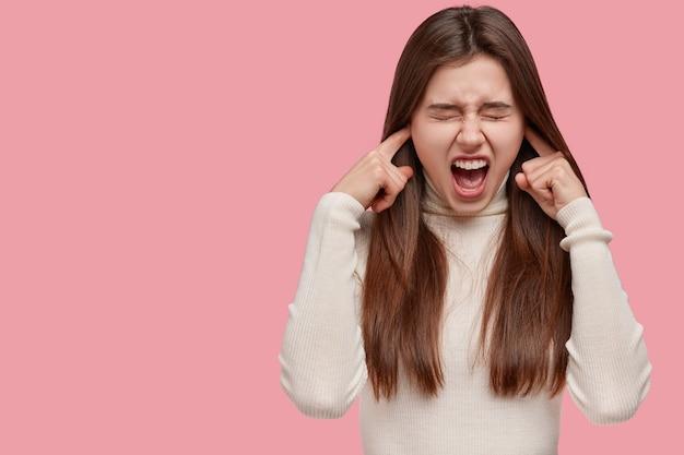Mulher bonita e frustrada tapa os ouvidos, exclama em voz alta, abre a boca, fecha os olhos, vestida com roupa casual, ignora sons irritantes