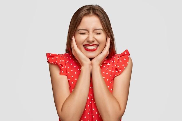 Mulher bonita e gentil com batom vermelho posando contra a parede branca