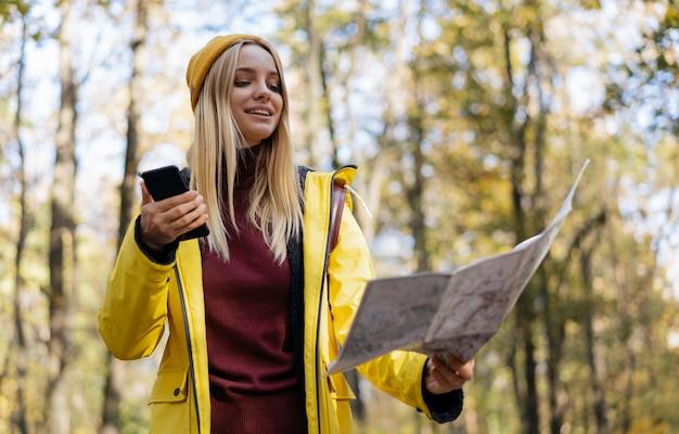 Mulher bonita e hippie usando mapa para navegar na floresta de outono conceito de viagens de férias