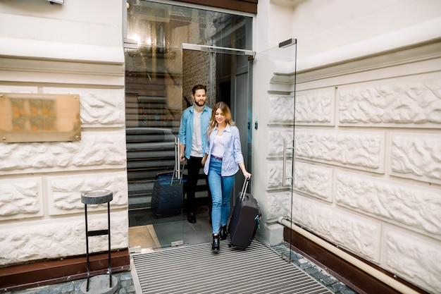Mulher bonita e homem bonito, de mãos dadas estão saindo de um hotel com suas malas
