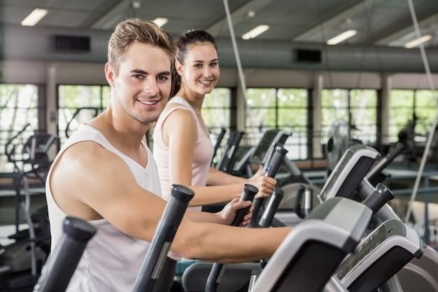 Mulher bonita e homem exercitando na máquina elíptica