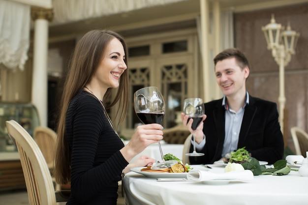 Mulher bonita e homem no restaurante, segurando o copo de vinho
