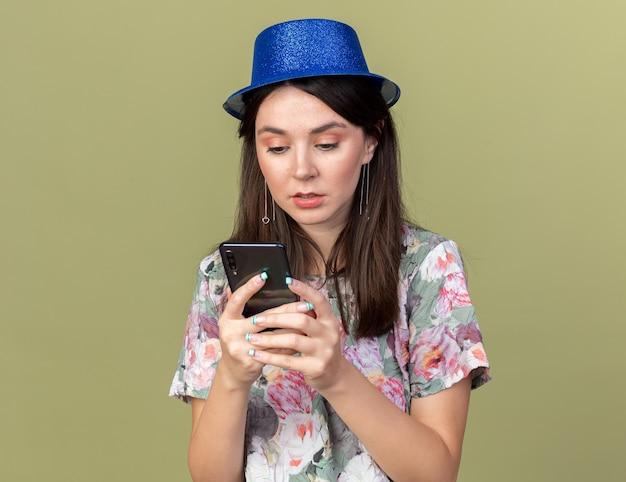 Mulher bonita e jovem confusa usando chapéu de festa segurando e olhando para o telefone isolado na parede verde oliva